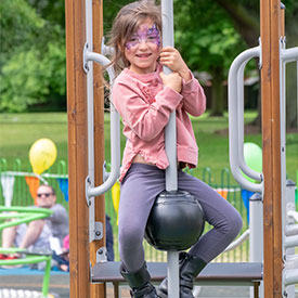 Girl climbing a ball climber onto the deck of a multi play unit