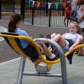 Girls playing on an inclusive playground seesaw