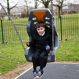 Boy on an inclusive swing seat with back rest