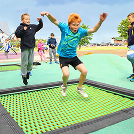 Children jumping on an outdoor playground trampoline