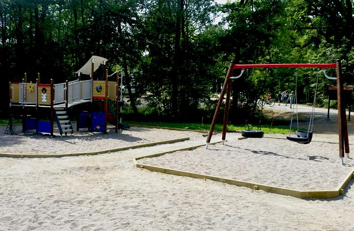 A swing frame with dark timber legs and a red top beam sits in a sandy playground.